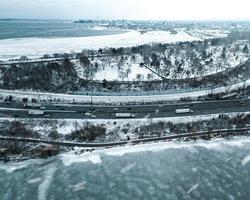 luchtfoto van voertuigen die overdag op winterwegen passeren