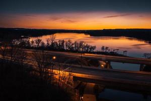 oranje hemel over brug en rivier in de schemering