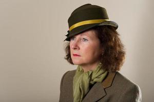 brunette in groene vilten hoed naar beneden te kijken