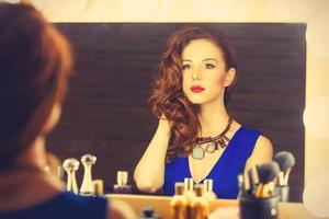 vrouw als het aanbrengen van make-up in de buurt van een spiegel