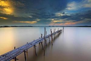 zonsondergang bij bamboebrug op zee