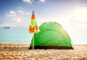 mooie achtergrond zomer concept, tent op strand bij zonsondergang