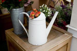 oranje rozen in zilveren gieter op houten tafel foto