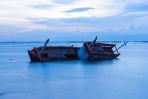 schipbreuk in de zee bij schemering