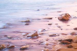 gladde zee en stenen bij zonsopgang