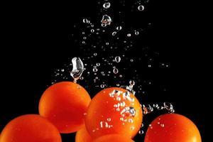 cherrytomaatjes vallen in water op zwarte achtergrond foto