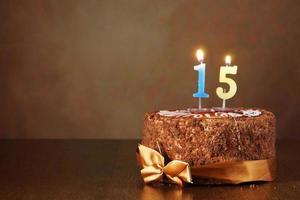 chocolade verjaardagstaart met brandende kaarsen als een nummer vijftien foto
