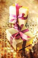 kerstcadeautjes met paars lint op gouden achtergrond foto