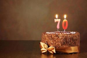 chocolade verjaardagstaart met brandende kaarsen als een nummer zeventig foto