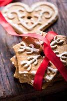 peperkoekkoekjes met rood lint op houten achtergrond