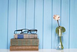 stapel boeken, glazen en witte roos in de fles foto