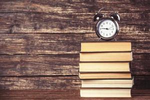wekker en boeken over houten tafel. foto