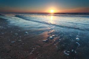 zonsondergang over het zandstrand van de Noordzee foto