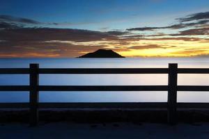 zee en berg bij zonsondergang met parkeerplaats foto