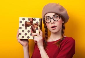 roodharige meisje met koffer op gele achtergrond. foto