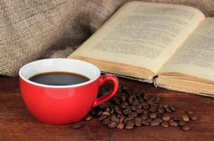 kopje koffie met koffiebonen en boek op tafel foto