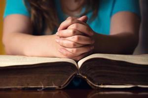 biddende handen op de bijbel