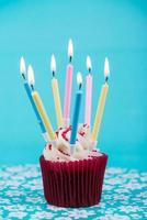 cup verjaardagstaart met veel kaarsen op blauwe achtergrond