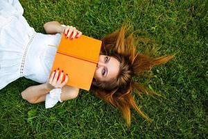meisje verbergt haar gezicht achter boek liggend op gazon.