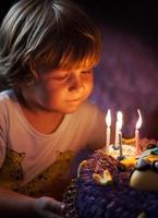 kleine jongen blaast kaarsjes uit op zijn verjaardag foto