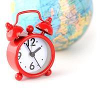 rode wekker en globe wereldtijd foto
