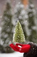 kerstboom in de hand bij sneeuw achtergrond