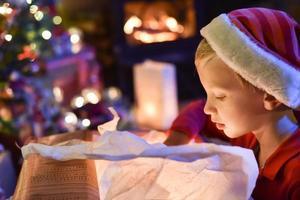 kersttijd, kleine jongen die een geschenk opent in de buurt van een boom verlicht foto