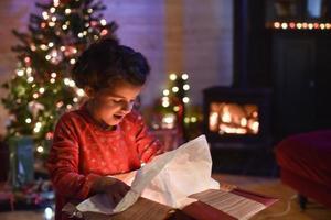 kersttijd, klein meisje dat een geschenk opent in de buurt van een boom verlicht foto