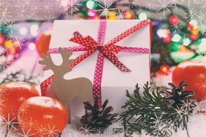 kerstcadeautjes met rood lint en mandarijnen en kegels, dec foto