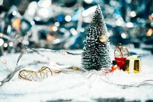 miniatuurkerstboom, sneeuwman en giften in de sneeuw foto