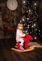 klein meisje op een stuk speelgoed paard