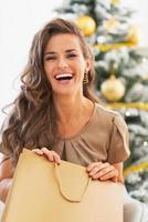 gelukkige jonge vrouw met boodschappentas in de buurt van kerstboom