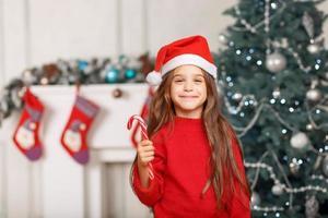 leuk meisje speelt in de buurt van de kerstboom foto