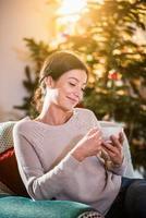 op kerstochtend, vrouw met een kopje thee foto