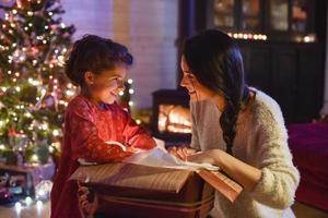 kersttijd, moeder en haar dochter openen een geschenk in de buurt van een boom foto
