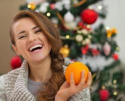 portret van lachende jonge vrouw met sinaasappel in de buurt van kerstboom foto