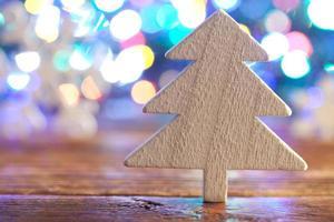 houten kerstboom op verlichtingsachtergrond foto