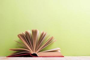 open hardcover boek over houten tafel en groene achtergrond