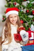 klein meisje met lang haar in de buurt van de kerstboom
