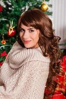 portret van lachende jonge vrouw in de buurt van de kerstboom