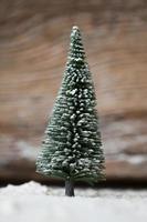 kerstkaart - een miniatuur kerstboom in de sneeuw