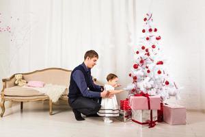 klein meisje speelt met haar vader in de buurt van de kerstboom foto