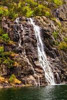 rotsen, zee en de snelle stroom van waterval foto