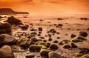 rotsachtige kust van de Oostzee bij zonsondergang