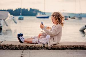 kind meisje speelt met speelgoed vogel op zee