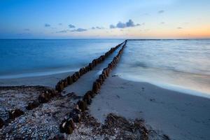 lange houten golfbreker in de Noordzee foto