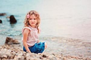 gelukkig kind meisje op stenen strand met zee op de achtergrond