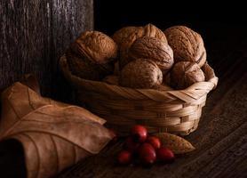 herfststilleven met walnoot, blad en rozenbottel.