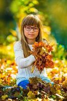 vrij jong meisje met herfst esdoorn bladeren