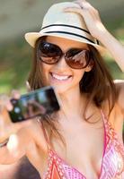 vrij jong meisje dat selfies met haar slimme telefoon neemt.